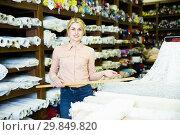 Купить «Saleswoman offering cloth in textile shop», фото № 29849820, снято 2 марта 2018 г. (c) Яков Филимонов / Фотобанк Лори