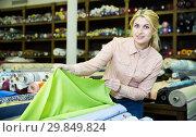 Купить «Woman looking for cloth in shop», фото № 29849824, снято 2 марта 2018 г. (c) Яков Филимонов / Фотобанк Лори