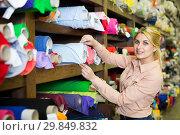 Купить «Woman looking for cloth in shop», фото № 29849832, снято 2 марта 2018 г. (c) Яков Филимонов / Фотобанк Лори