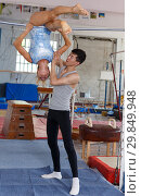 Купить «Man and woman doing acrobatic exercises in gym», фото № 29849948, снято 18 июля 2018 г. (c) Яков Филимонов / Фотобанк Лори