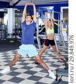 Купить «Portrait of young athletic couple practicing stretch exercises i», фото № 29849976, снято 16 июля 2018 г. (c) Яков Филимонов / Фотобанк Лори
