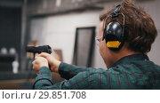 Shooting gallery. A concentrated young man shooting with a gun. Стоковое видео, видеограф Константин Шишкин / Фотобанк Лори