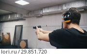 Купить «Shooting gallery. A concentrated young man shooting with a firearms», видеоролик № 29851720, снято 16 декабря 2019 г. (c) Константин Шишкин / Фотобанк Лори