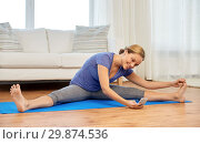 Купить «woman with smartphone doing yoga at home», фото № 29874536, снято 13 ноября 2015 г. (c) Syda Productions / Фотобанк Лори