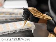 Купить «confectioner filling mold by cream at pastry shop», фото № 29874596, снято 4 декабря 2018 г. (c) Syda Productions / Фотобанк Лори