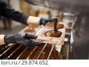 Купить «confectioner makes chocolate candies at sweet-shop», фото № 29874652, снято 4 декабря 2018 г. (c) Syda Productions / Фотобанк Лори