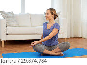 Купить «woman doing twist in lotus pose at home», фото № 29874784, снято 13 ноября 2015 г. (c) Syda Productions / Фотобанк Лори