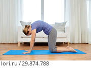 Купить «woman doing yoga cat pose at home», фото № 29874788, снято 13 ноября 2015 г. (c) Syda Productions / Фотобанк Лори