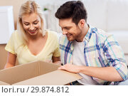Купить «happy couple looking inside box or parcel at home», фото № 29874812, снято 25 февраля 2016 г. (c) Syda Productions / Фотобанк Лори