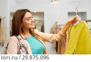Купить «happy woman choosing clothes at clothing store», фото № 29875096, снято 19 февраля 2016 г. (c) Syda Productions / Фотобанк Лори