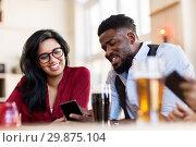 Купить «happy man and woman with smartphones at bar», фото № 29875104, снято 2 мая 2017 г. (c) Syda Productions / Фотобанк Лори