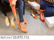 Купить «young woman trying high-heeled shoes at store», фото № 29875112, снято 22 сентября 2017 г. (c) Syda Productions / Фотобанк Лори