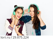 Купить «teenage girls in earphones listening to music», фото № 29875224, снято 19 декабря 2015 г. (c) Syda Productions / Фотобанк Лори
