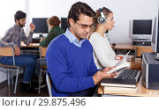 Serious student reading textbooks in computer class. Стоковое фото, фотограф Яков Филимонов / Фотобанк Лори
