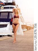 Купить «Beautiful sexy girl with a slim figure is standing on a wooden pier in a yacht club», фото № 29876156, снято 27 июня 2017 г. (c) katalinks / Фотобанк Лори