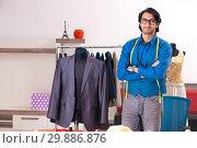 Купить «Young male tailor working at workshop», фото № 29886876, снято 22 ноября 2018 г. (c) Elnur / Фотобанк Лори