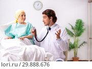 Купить «Young handsome doctor visiting female oncology patient», фото № 29888676, снято 3 октября 2018 г. (c) Elnur / Фотобанк Лори