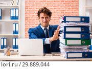 Купить «Young elegant man unhappy with too much work», фото № 29889044, снято 14 сентября 2018 г. (c) Elnur / Фотобанк Лори