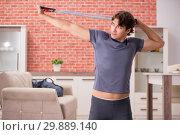 Купить «Young handsome man doing sport exercises at home», фото № 29889140, снято 12 сентября 2018 г. (c) Elnur / Фотобанк Лори