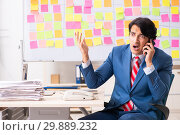 Купить «Young handsome employee with many conflicting priorities», фото № 29889232, снято 16 октября 2018 г. (c) Elnur / Фотобанк Лори