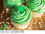 Купить «green cupcakes and shamrock on wooden table», фото № 29889956, снято 31 января 2018 г. (c) Syda Productions / Фотобанк Лори
