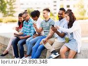 Купить «friends with smartphones hanging out in summer», фото № 29890348, снято 10 июня 2018 г. (c) Syda Productions / Фотобанк Лори