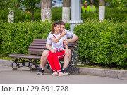 Купить «Russia, Samara, May 2018: A loving couple is sitting on a bench and making selfies.», фото № 29891728, снято 24 мая 2018 г. (c) Акиньшин Владимир / Фотобанк Лори