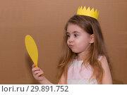 Portrait of emotional little girl with crown a yellow paper holding a mirror. handmade. cardboard background. Стоковое фото, фотограф Константин Сиятский / Фотобанк Лори