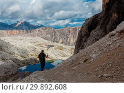 Купить «Hikers descending the path SAT 666, at the bottom you see the turquoise mirror of the lake Piasciadu and back the Franco Cavazza hut in the Sella Group, Dolomites, Trentino-Alto Adige, Italy», фото № 29892608, снято 19 марта 2019 г. (c) age Fotostock / Фотобанк Лори