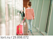 Adorable little girl in airport with her luggage waiting for boarding. Стоковое фото, фотограф Дмитрий Травников / Фотобанк Лори