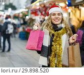 Купить «Girl holding paper bags at Christmas fair», фото № 29898520, снято 20 декабря 2018 г. (c) Яков Филимонов / Фотобанк Лори