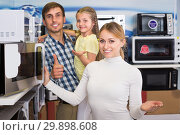 Купить «Smiling couple with kid in hypermarket», фото № 29898608, снято 13 ноября 2019 г. (c) Яков Филимонов / Фотобанк Лори