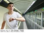 Купить «Man looking at watch on underground station», фото № 29898748, снято 24 августа 2018 г. (c) Яков Филимонов / Фотобанк Лори