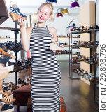 Купить «Woman customer choosing from two pairs of sandals», фото № 29898796, снято 18 февраля 2019 г. (c) Яков Филимонов / Фотобанк Лори
