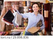 Купить «Glad woman shopping carpet and showing samples», фото № 29898836, снято 22 ноября 2017 г. (c) Яков Филимонов / Фотобанк Лори