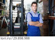 Portrait of man worker in uniform standing near shelving. Стоковое фото, фотограф Яков Филимонов / Фотобанк Лори
