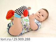 Купить «Младенец играет ногами в цветных носках с погремушками», фото № 29909288, снято 16 марта 2015 г. (c) Ирина Борсученко / Фотобанк Лори