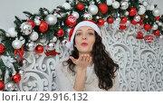 Купить «Happy girl in red santa hat send air kissing looking at the camera in Christmas decorated studio», видеоролик № 29916132, снято 3 декабря 2018 г. (c) Ольга Балынская / Фотобанк Лори