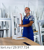Купить «Workman in blue overalls demonstrating pvc window», фото № 29917724, снято 19 июля 2017 г. (c) Яков Филимонов / Фотобанк Лори