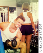 Купить «smiling man making biceps curls in gym», фото № 29917864, снято 4 октября 2016 г. (c) Яков Филимонов / Фотобанк Лори