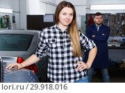 Smiling female is satisfied of tire replacement of her car in spring. Стоковое фото, фотограф Яков Филимонов / Фотобанк Лори