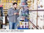 Купить «Smiling man client choosing new glue in store», фото № 29918060, снято 5 апреля 2017 г. (c) Яков Филимонов / Фотобанк Лори