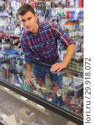 Купить «guy demonstrating handgun in army market», фото № 29918072, снято 4 июля 2017 г. (c) Яков Филимонов / Фотобанк Лори
