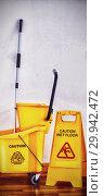 Купить «Yellow sign board with mop bucket on floor against wall», фото № 29942472, снято 18 июля 2019 г. (c) Wavebreak Media / Фотобанк Лори