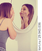 Купить «Young female touching face, using mirror in bedroom», фото № 29943036, снято 5 марта 2018 г. (c) Яков Филимонов / Фотобанк Лори