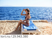 Купить «Beautiful woman sunbathing on a beach at tropical travel resort, enjoying summer holidays. Young woman lying on sun lounger near the sea. Happy serene woman», фото № 29943380, снято 9 февраля 2019 г. (c) Happy Letters / Фотобанк Лори
