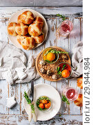 Купить «Easter table setting with colored orange eggs, hot cross buns, green branches decorated, empty plate, cutlery, glass of lemonade drink over white plank wooden table with textile tablecloth. Flat lay», фото № 29944984, снято 12 июля 2020 г. (c) age Fotostock / Фотобанк Лори