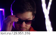 Купить «portrait of man putting sunglasses on in dark room», видеоролик № 29951316, снято 11 февраля 2019 г. (c) Syda Productions / Фотобанк Лори