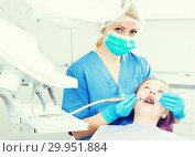Купить «Female dentist performing treatment to girl», фото № 29951884, снято 1 марта 2018 г. (c) Яков Филимонов / Фотобанк Лори