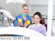 Купить «Happy girl with female dentist showing apples», фото № 29951888, снято 1 марта 2018 г. (c) Яков Филимонов / Фотобанк Лори